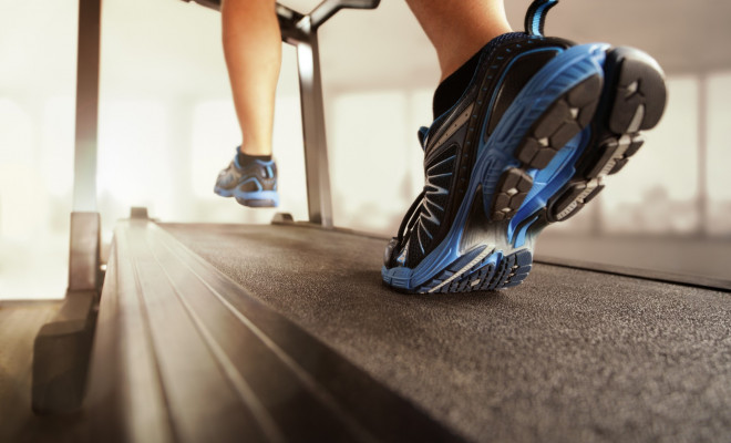 man-wearing-blue-shoes-running-on-treadmill-in-a-gym-room-fitness