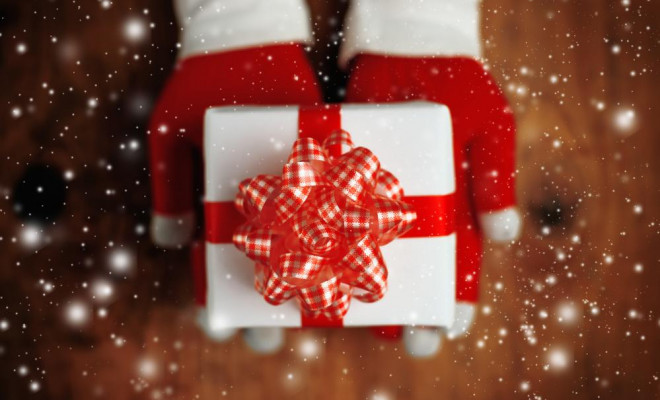 woman-offering-christmas-gift-in-wrapped-box